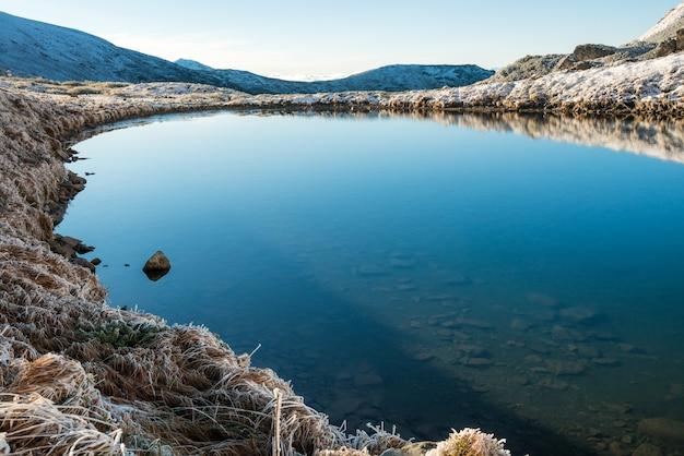 Schöner blauer see in den bergen, morgensonnenaufgangzeit. landschaft mit schnee und gefrorener natur