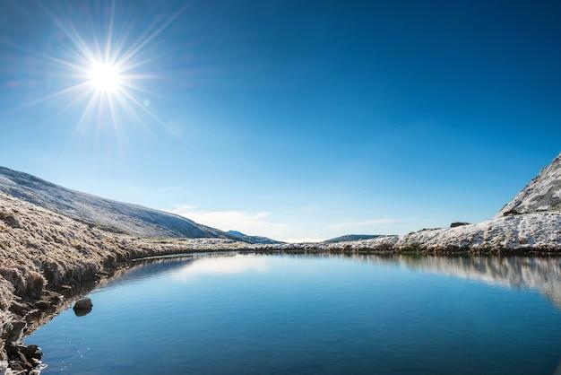 Schöner blauer see in den bergen, morgensonnenaufgangzeit. landschaft mit schneebedeckter sonne