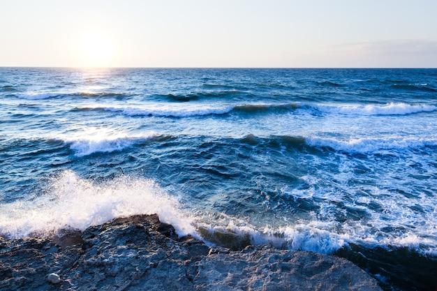 Schöner blauer sonnenuntergang und wassersteine über felsiger küste des schwarzen meeres auf der krim am sommertag