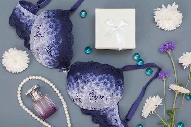 Schöner blauer spitzen-bh, flasche parfüm, perlen und geschenkbox auf grauem hintergrund. frauen sexy unterwäsche-set. romantische dessous für die versuchung.