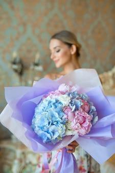 Schöner blauer strauß in den händen der frau