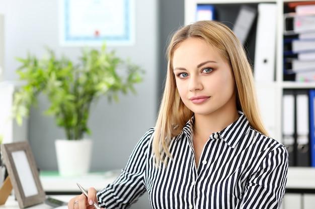 Schöner blonder eleganter weiblicher sekretär am arbeitsplatz