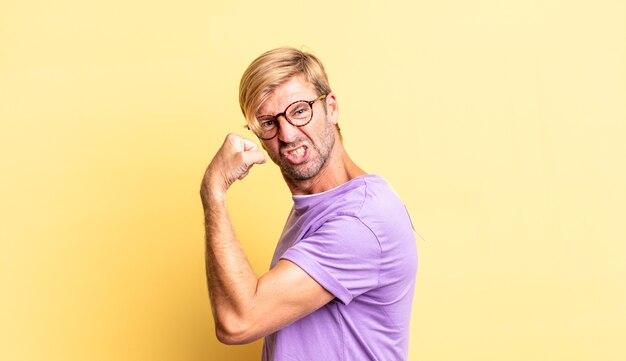 Schöner blonder erwachsener mann, der sich glücklich, zufrieden und kraftvoll fühlt, fit und muskulös ist und nach dem fitnessstudio stark aussieht