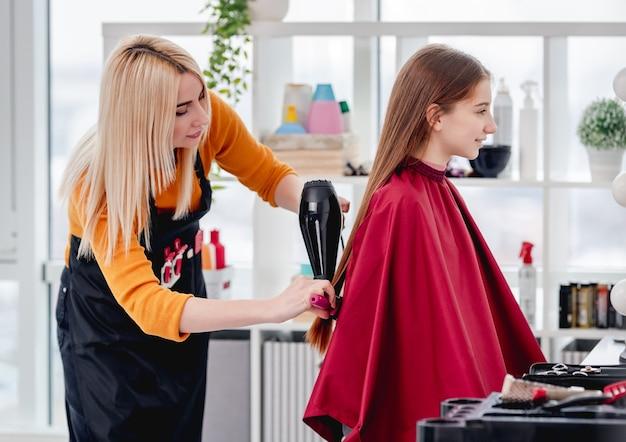 Schöner blonder friseur glättet das haar des modells der jungen frau unter verwendung des haartrockners