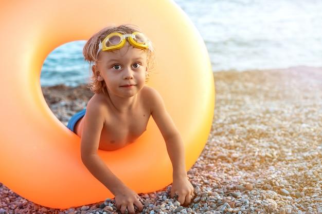 Schöner blonder kleiner junge in einem gummirad auf der küste, die spaß hat und mit kieseln spielt.