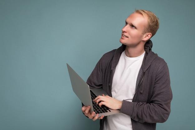 Schöner blonder mann, der computer-laptop hält und auf tastatur denkt