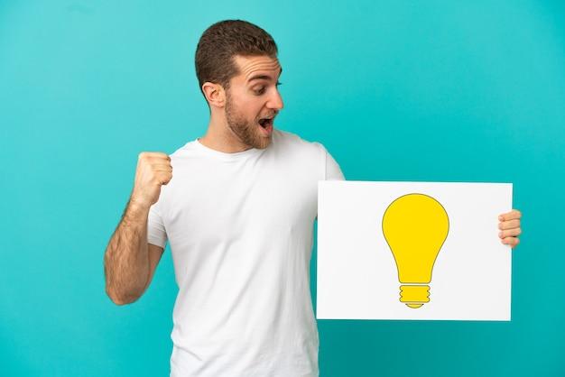 Schöner blonder mann über isoliertem blauem hintergrund, der ein plakat mit glühbirnensymbol hält und einen sieg feiert