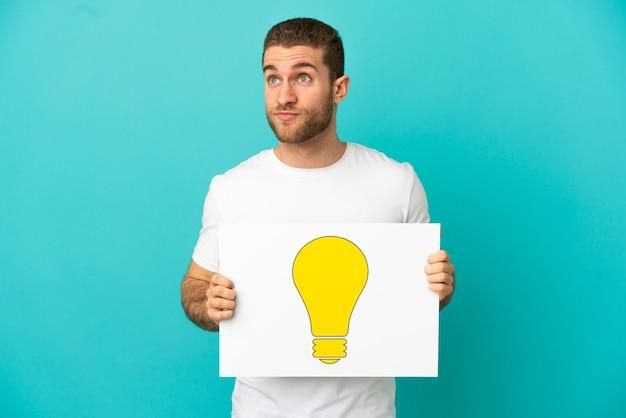 Schöner blonder mann über isoliertem blauem hintergrund, der ein plakat mit glühbirnensymbol hält und nach oben schaut