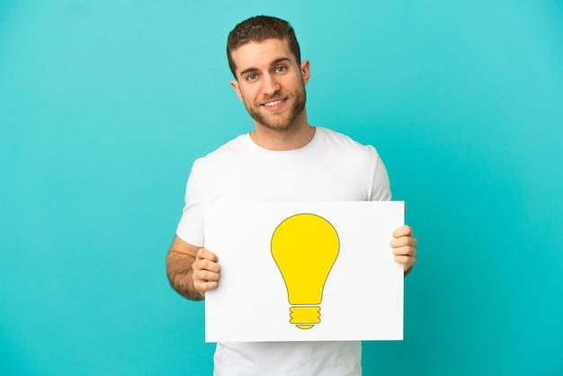 Schöner blonder mann über isoliertem blauem hintergrund, der ein plakat mit glühbirnensymbol mit glücklichem ausdruck hält