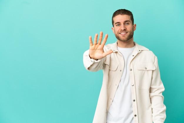 Schöner blonder mann über isoliertem blauem hintergrund, der fünf mit den fingern zählt count