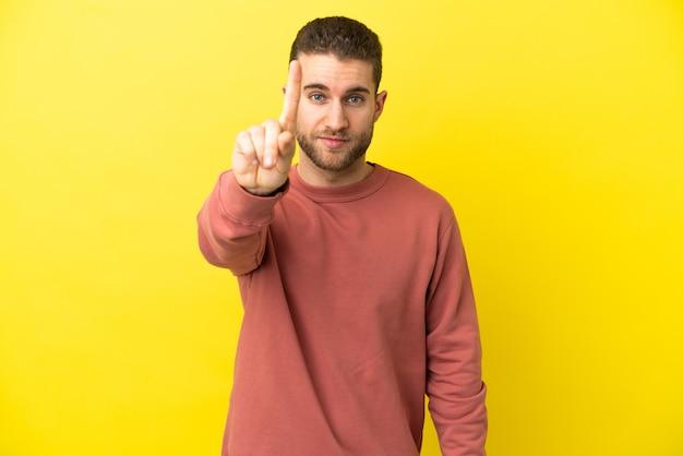 Schöner blonder mann über isoliertem gelbem hintergrund, der eins mit ernstem ausdruck zählt
