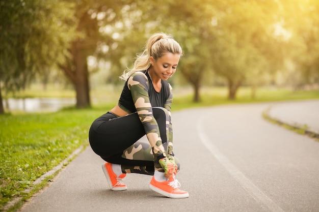 Schöner blonder sportabnutzungsbetrieb der gesunden eignung in mode und übt yoga im park bei sonnenuntergang