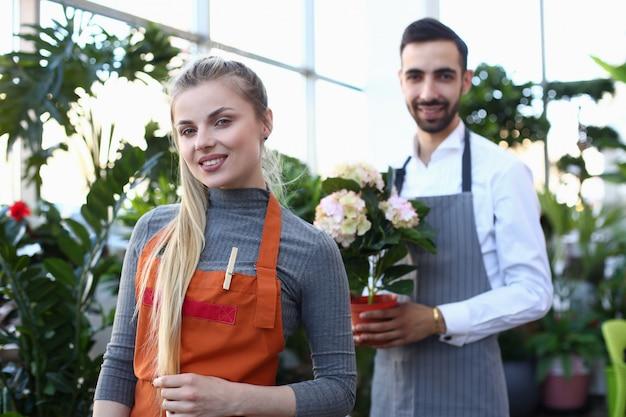 Schöner blondine-florist und mann mit blume. lächelnder mädchen-gärtner und mann, die weiße blühende hortensie in der inländischen betriebsmitte halten.