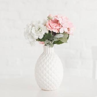 Schöner blühender vase auf weißer tabelle