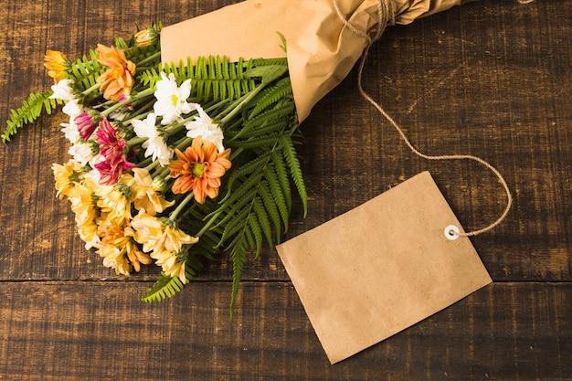 Schöner blumenblumenstrauß mit leerem aufkleber über hölzernem schreibtisch