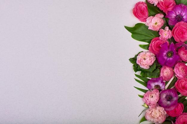 Schöner blumenhintergrund und grüne blätter flache lage der rosa blumen auf grauem hintergrund, draufsicht, kopie raumgrußkarte