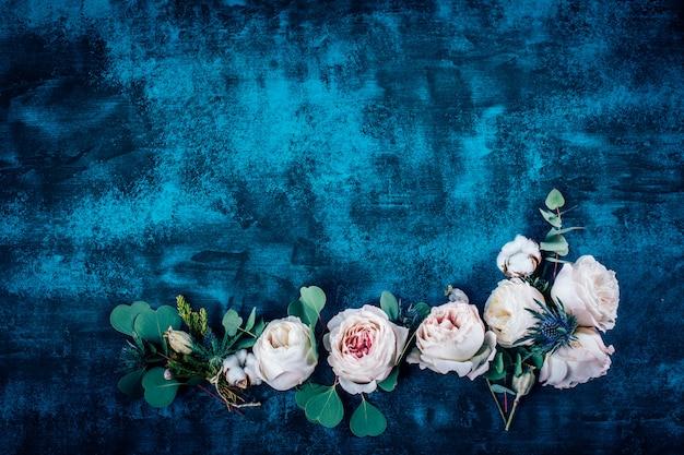 Schöner blumenrahmen mit rosen auf blauem hintergrund
