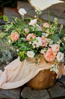 Schöner blumenstrauß auf einem hölzernen stumpf. rosa rosen. hochzeitstag.