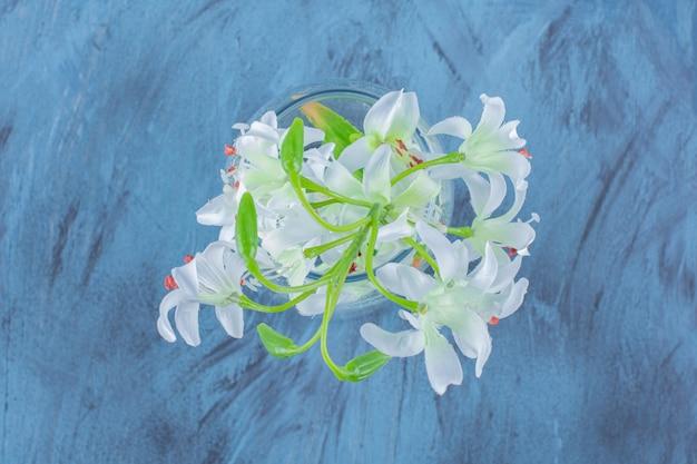 Schöner blumenstrauß aus lilienblumen in einer glasvase auf blau.