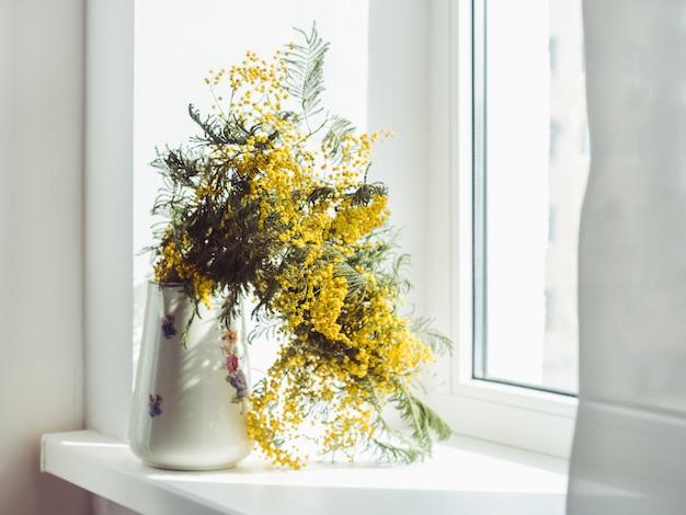Schöner blumenstrauß aus mimosen in einem vintage-vase