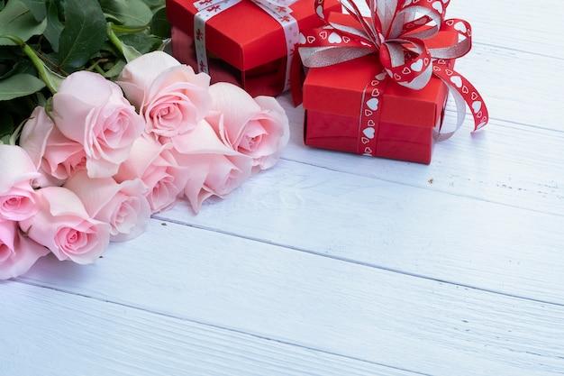 Schöner blumenstrauß aus rosa rosen und roten präsentkartons