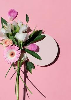 Schöner blumenstrauß blumenstrauß aus pfingstrosen-rosen-gerberas mit leerem rundem mock-up einzeln auf rosafarbenem hintergrund flache ansicht von oben