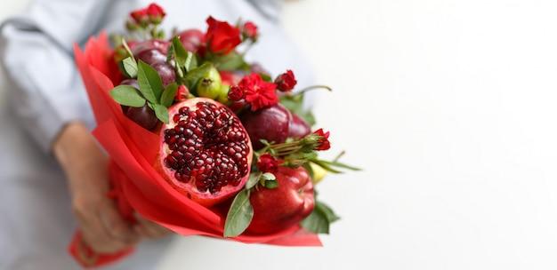 Schöner blumenstrauß, der aus früchten und rosen in den händen einer frau besteht