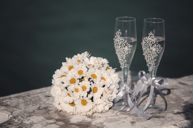 Schöner blumenstrauß der frischen blumen und zwei gläser champagner