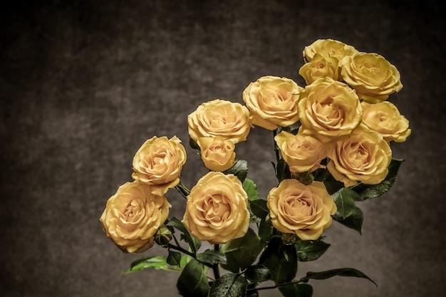 Schöner blumenstrauß der gelben rosen auf einem grauen hintergrund