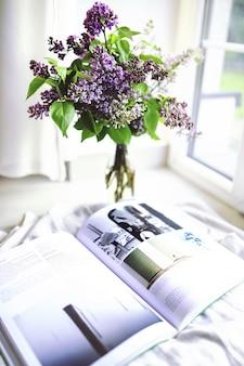 Schöner blumenstrauß der lila blüten mit einem offenen magazin