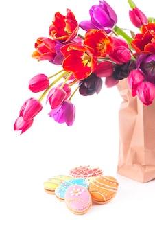 Schöner blumenstrauß der lila tulpen in der papiertüte, lokalisiert auf weiß
