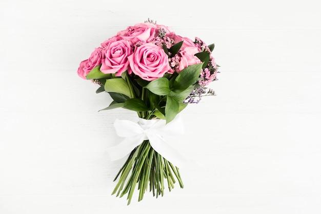 Schöner blumenstrauß der rosa rosenblumen mit weißer schleife