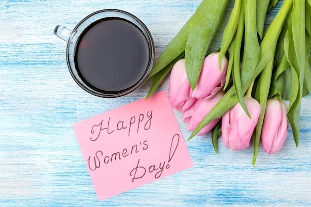Schöner blumenstrauß der rosa tulpen, eine tasse kaffee und der text des glücklichen frauentages auf papier auf einer blauen holzoberfläche