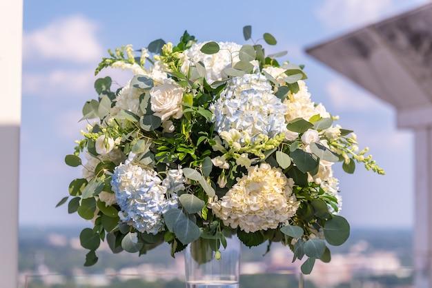 Schöner blumenstrauß der weißen blumen in einer vase während einer hochzeitszeremonie