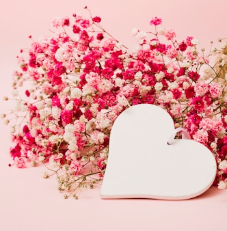Schöner blumenstrauß des baby-atems blüht mit weißer herzform auf rosa hintergrund