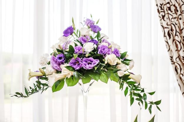 Schöner blumenstrauß in einer glasvase. lila und weiße blumen.