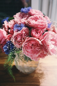 Schöner blumenstrauß mit den rosa pfingstrosen und kornblumen, die auf dem fenster stehen