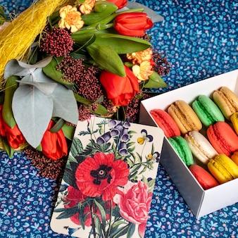 Schöner blumenstrauß mit macaron und postkarte
