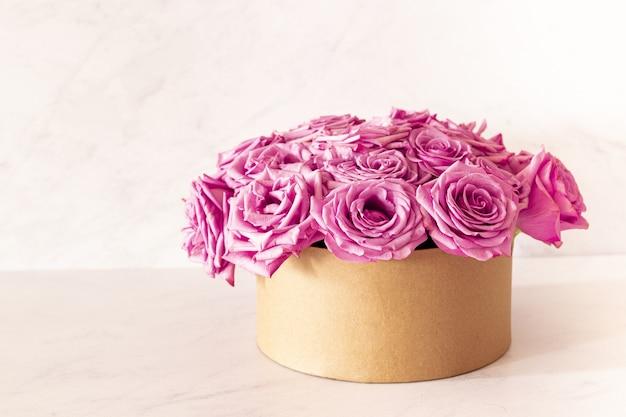 Schöner blumenstrauß mit rosa rosen in einer schachtel auf einem rosa hintergrund