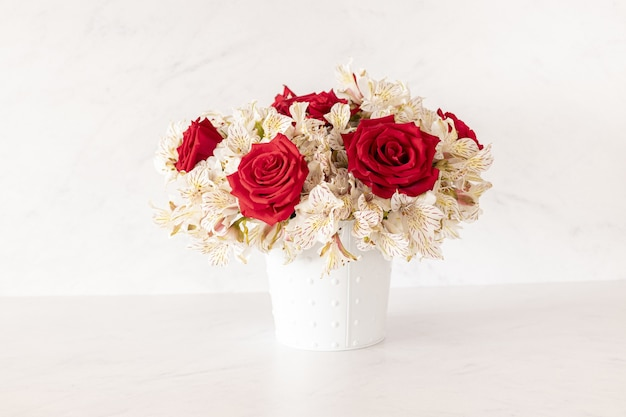 Schöner blumenstrauß mit roten rosen und lilienblumen in einer schachtel