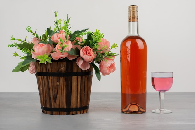Schöner blumenstrauß und flasche roséwein auf grauem tisch