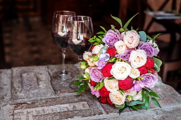 Schöner blumenstrauß und zwei gläser wein. romantisches date.