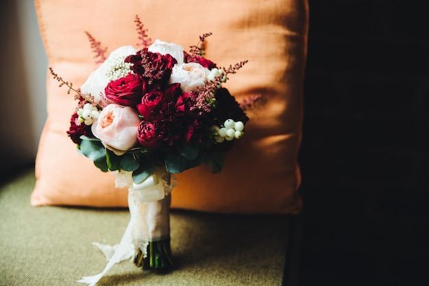 Schöner blumenstrauß von den roten und weißen rosen, die mit band gebunden werden, stehen innen am lehnsessel gegen kissen