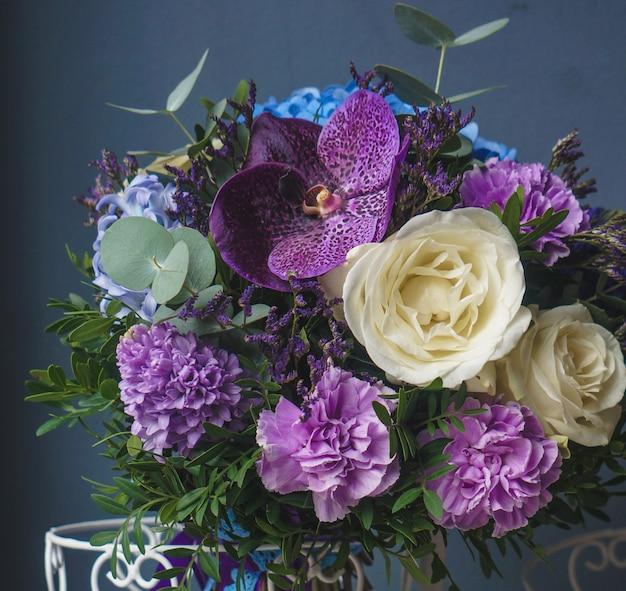 Schöner blumenstrauß von fliedern und von rosen, die in einem rustikalen folglich vase stehen