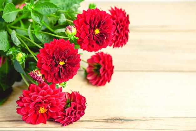 Schöner blumenstrauß von frisch geschnittenen roten dahlien auf holztisch