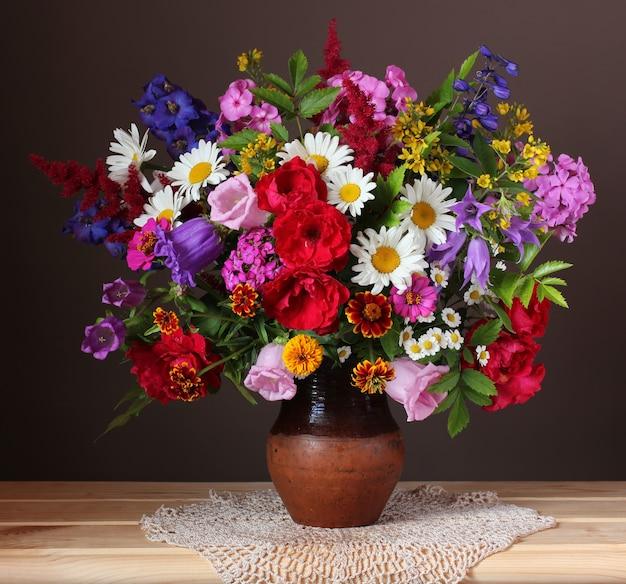 Schöner blumenstrauß von gartenblumen in einem krug. rosen, gänseblümchen, phlox und glocken.