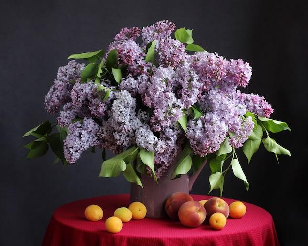 Schöner blumenstrauß von purpurroten fliedern im glas. stillleben mit blumen in einer vase, mit aprikosen und pfirsichen auf dem runden tisch.