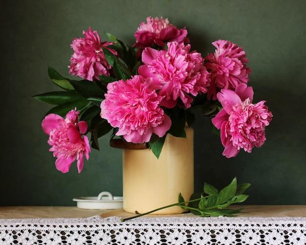 Schöner blumenstrauß von rosa pfingstrosen auf dem tisch mit einer spitzentischdecke. gartenblumen