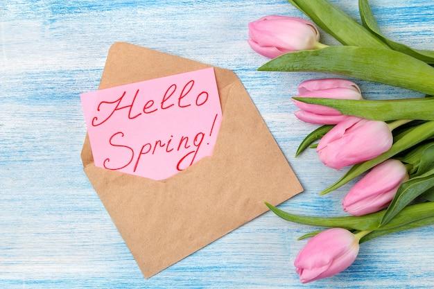 Schöner blumenstrauß von rosa tulpen und text hallo frühling auf papier in einem umschlag auf einer blauen holzoberfläche