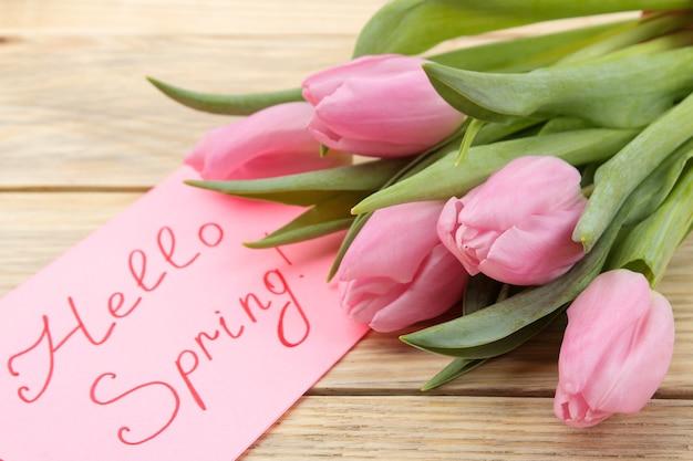Schöner blumenstrauß von rosa tulpenblumen und text hallo frühling im notizbuch auf natürlicher holzoberfläche